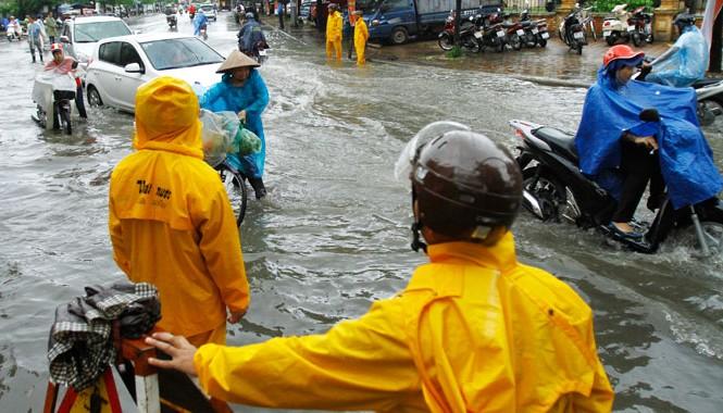 Công nhân cấp thoát nước Hà Nội đứng túc trực tại điểm ngập trên đường Lê Trọng Tấn. ảnh: Như Ý