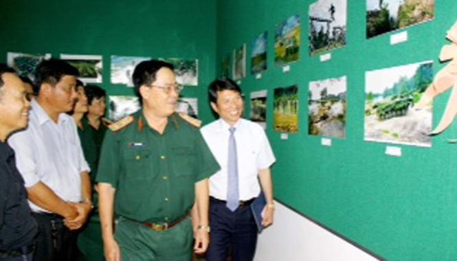 NSNA Vũ Quốc Khánh- Chủ tịch Hội NSNA Việt Nam cùng Trung tướng Đinh Văn Cai, Chính ủy Quân khu 9 và đại biểu tham quan triển lãm. Ảnh: Dương Thu