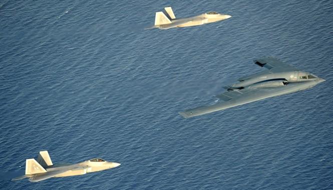B-2 Spirit được hai chiếc tiêm kích tàng hình F-22 hộ tống tại Guam. Ảnh: US Navy