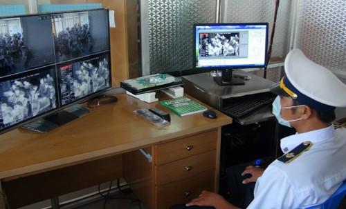 Nhân viên Y tế theo dõi, kiểm tra thân nhiệt hành khách trên màn hình. Ảnh: Phạm Thanh Tân-TTXVN