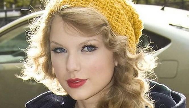 """""""Công chúa nhạc đồng quê"""" Taylor Swift là người rất thích những chiếc mũ len. Mái tóc vàng óng gợn sóng của Taylor cũng khá ton-sur-ton với màu mũ vàng mustard. Nếu bạn sở hữu mái tóc rẽ ngôi lệch, hãy đội sao cho viền mũ nằm ngang với đường chân tóc trướ"""