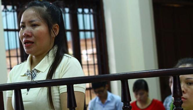 Nguyệt (đứng, khóc) và Trang tại phiên toà sơ thẩm.