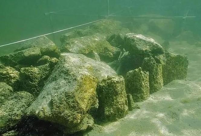 Một phần của cấu trúc thời đồ đá đã lộ diện khi trầm tích bị lấy bớt. Ảnh: CEN.