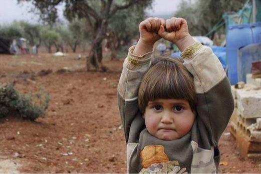 Cô bé Adi Hudea giơ tay đầu hàng vì tưởng ống kính máy ảnh là nòng súng