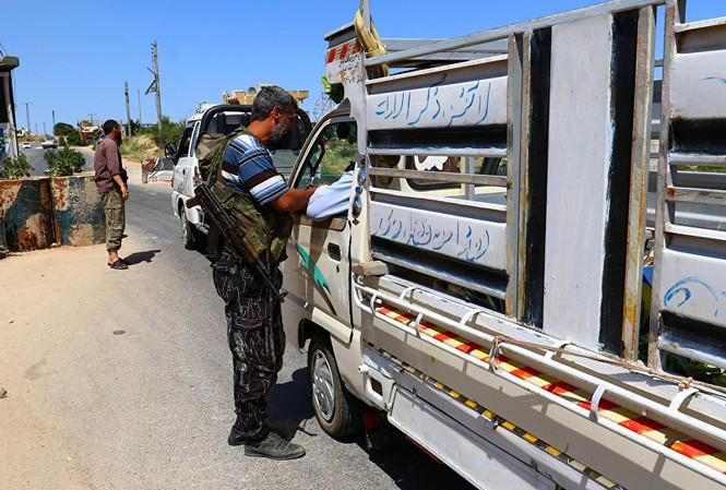 Các tay súng của liên minh các nhóm nổi dậy Jaish al Fateh kiểm tra xe tải tại tỉnh Idlib hôm 18/7. Ảnh: Reuters