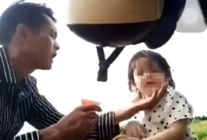 T. ép con gái 3 tuổi uống nước từ chai thuốc màu xanh. (Ảnh: Cắt từ clip)