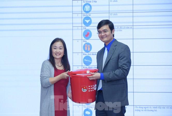 Anh Bùi Quang Huy tiếp nhận bộ đồ thiết yếu cho người cao tuổi ứng phó với lũ lụt từ bà Naomi Kitahara. Ảnh: Xuân Tùng
