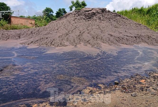 Sau cơn mưa, lượng nước màu đen từ chất thải đổ lênh láng trên nền đất