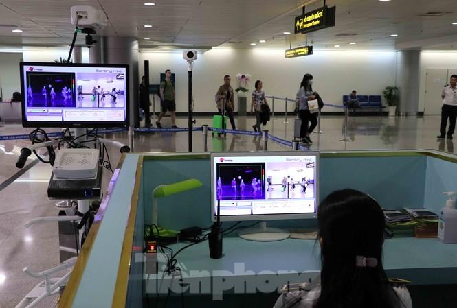 Nhân viên y tế theo dõi thân nhiệt khách quốc tế nhập cảnh vào sân bay Tân Sơn Nhất.