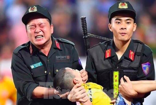 Chiến sỹ cảnh sát cơ động nghiến răng chịu đau để tránh cháu bé cắn vào lưỡi - Ảnh: Hoàng Long