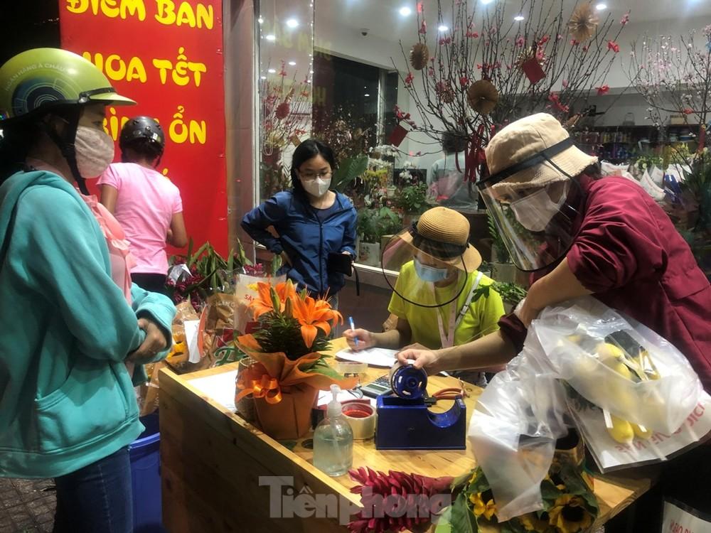 Nhân viên đội mũ chống giọt bắn bán hoa đại hạ giá ở TP.HCM