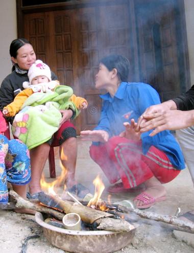 Trẻ nhỏ được cha mẹ mặc nhiều lớp quần áo rồi quấn thêm chăn, mền, ngồi sưởi bên bếp lửa