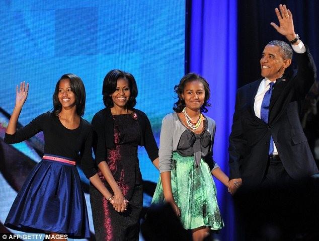 Ông Obama cùng vợ con bước lên sân khấu chào những người ủng hộ