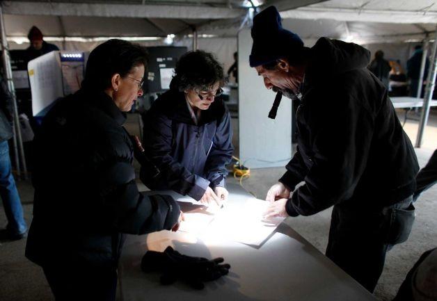 Các cử tri vẫn nỗ lực bỏ phiếu bầu cử tổng thống mặc dù phải dùng đèn pin