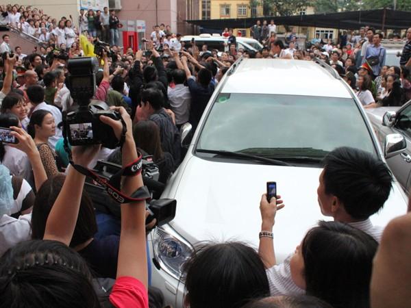 Hàng trăm người bao quanh chiếc ô tô đưa cháu bé về Bệnh viện. Ảnh: L.G