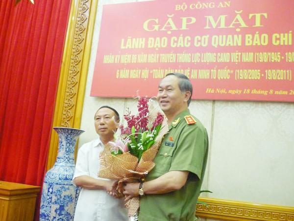 Bộ trưởng Trần Đại Quang (phải) nhận hoa chúc mừng do ông Hoàng Hữu Lượng (Cục trưởng Cục Báo chí, Bộ TT&TT) tặng