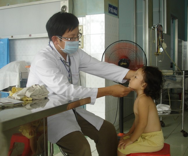 Bác sĩ Võ Minh Tiến đang khám cho cháu Ngân. Ảnh: Song Nguyên