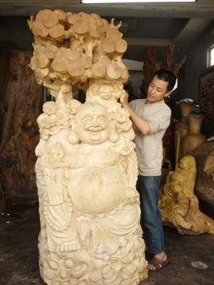 Nghệ nhân trẻ Hữu Thái bên bức tượng gỗ. Ảnh: Đình Văn