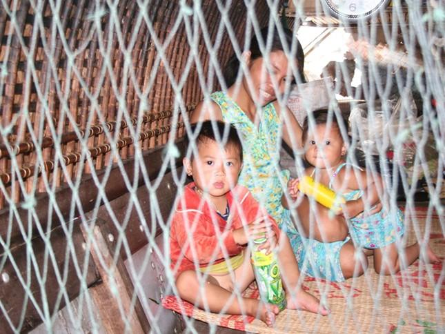 Mang con theo trên những chuyến ra khơi, những đứa trẻ được bảo vệ bằng những mảnh lưới tạm bợ. Ảnh: Nguyễn Huy