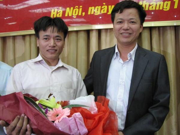 Anh Nguyễn Xuân Việt nhận bó hoa tri ân của anh Phạm Xuân Chiều - bố cháu bé bị bắt cóc. Ảnh: Lãng Phong
