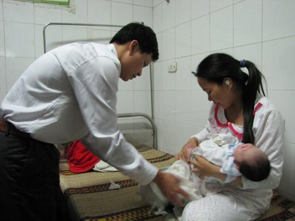 Vợ chồng anh Chiều chuẩn bị cho cháu Trường trước lúc xuất viện. Ảnh: Lãng Phong