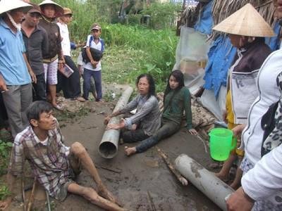 Vợ chồng bà Màu và con gái ở miệng ống bơm cát