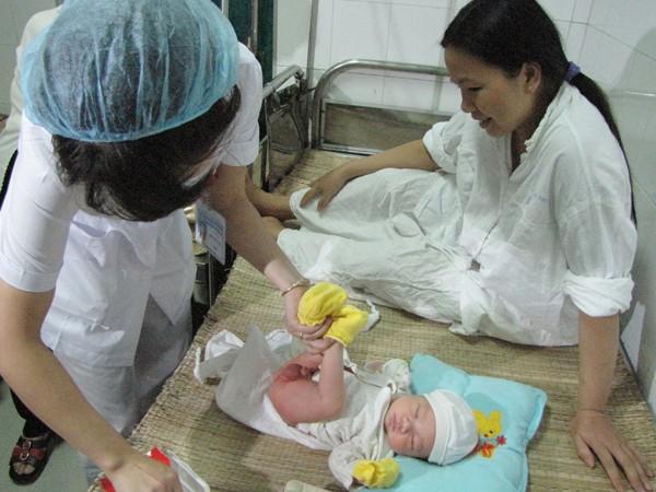Nhân viên bệnh viện thay tã cho cháu Trường Ảnh: Trường Phong.