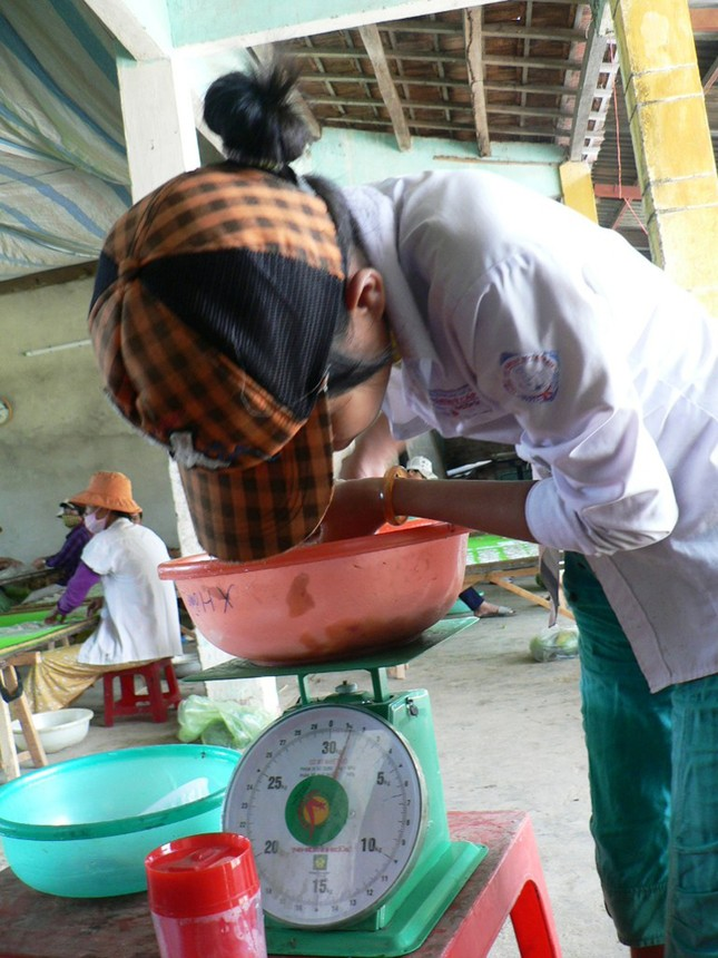 Em Nguyễn Thị Phương mặc nguyên bộ đồng phục tranh thủ đến làm tại xưởng chế biến cá bò