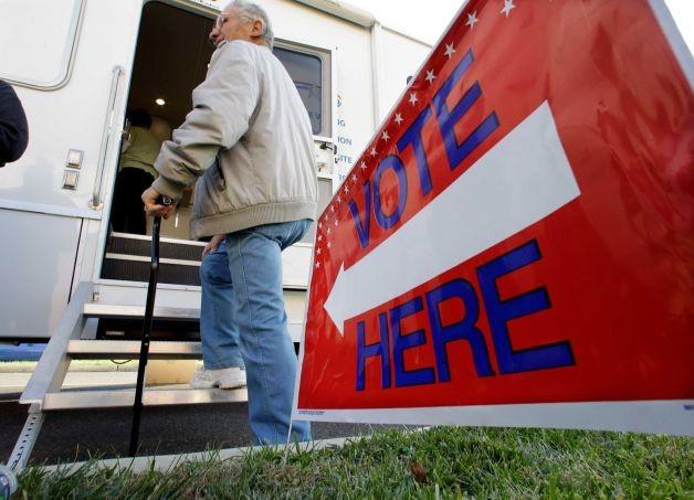 Một ông cụ chống gậy bước lên xe để bỏ phiếu bầu cử