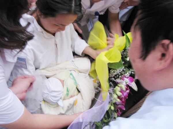 Khoảnh khắc chị Thơm nhận lại con từ đại diện bệnh viện và cơ quan điều tra. Ảnh: Lãng Phong