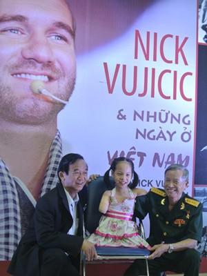 Bé Linh Chi chụp ảnh lưu niệm cùng GS Nguyễn Lân Dũng và một thương binh mất cánh tay. Ảnh: VOV