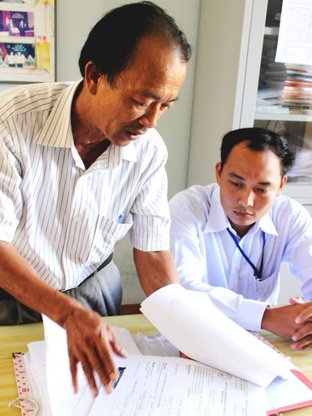 Ông Nguyễn Văn Cồn với chồng hồ sơ tồn đọng, thiếu dấu đỏ ở Hoàng Sa từ cuối 2010 tới nay. Ảnh: Nam Cường