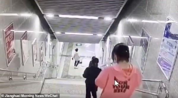 Vừa đi vừa cắm mặt vào điện thoại, cô gái bước hụt, ngã lao đầu xuống cầu thang ở ga tàu ảnh 1