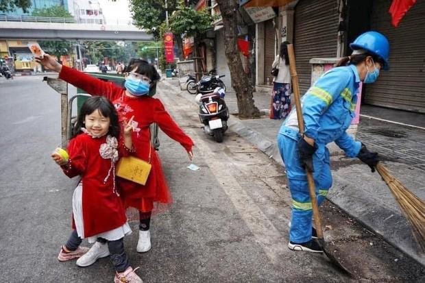 Bức ảnh 2 bé gái diện áo dài, phụ mẹ làm lao công đẩy xe rác trên phố gây xúc động ảnh 1