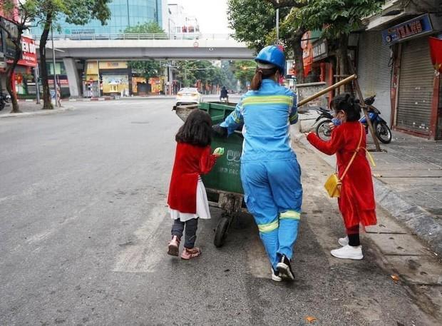 Bức ảnh 2 bé gái diện áo dài, phụ mẹ làm lao công đẩy xe rác trên phố gây xúc động ảnh 2