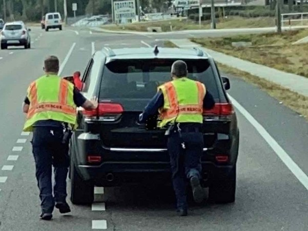 Những người lính cứu hỏa giúp đẩy xe ô tô tới trạm xăng.