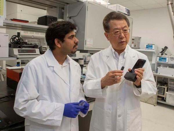 Giáo sư Chong Ahn (phải) và một đồng sự đang thảo luận về nền tảng khoa học của thiết bị mới.
