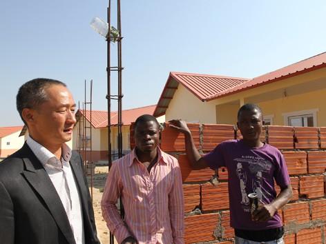 Anh Đức (người mặc vest) và khu căn hộ cho cán bộ công nhân viên quân khu Huambo do công ty anh xây dựng