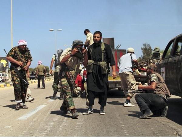 Lính NTC tránh trọng pháo, rocket và tên lửa của quân Gadhafi hôm 24-9 ở Sirte. Ảnh: Gaia Anderson