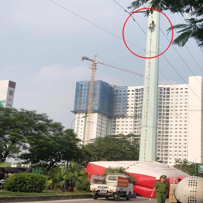 Người đàn ông cố thủ trên cột điện cao thế đường Lê Văn Lương kéo dài - ảnh 1