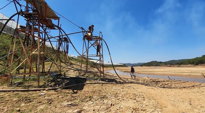 hồ nước sinh hoạt khô cạn, xe cộ băng qua lòng hồ. - ảnh 4