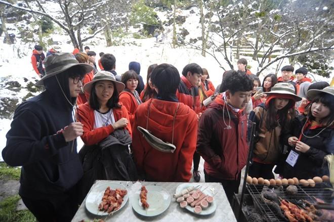 Trưa 16/12, du khách vẫn đổ về trung tâm thị trấn             Bài viết: http://news.zing.vn/Khach-du-lich-do-xo-len-Sa-Pa-trong-tuyet-trang-post377656.html#home_featured.noibat             Nguồn Zing News