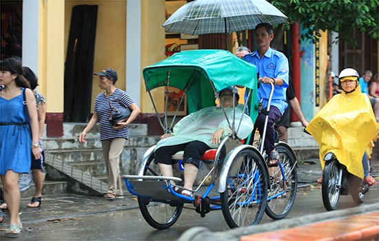 Mặc áo mưa ngồi xích lô dạo phố.
