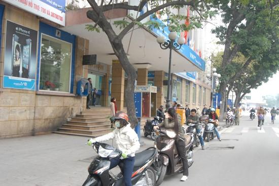 Nhiều xe máy lách luật bằng cách dừng đỗ dưới đường chờ người nhà vào Bưu điện giao dịch