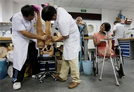 Hongyan vui vẻ ngồi nhìn các bác sĩ chỉnh sửa đôi chân giả của mình
