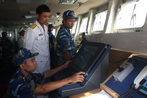Sau cuộc tuần tra, biên đội tàu của Hải quân Việt Nam bắt đầu tiến vào lãnh hải Trung Quốc. Trong ảnh: Thiếu tá Nguyễn Đình Giảng - Thuyền trưởng HQ-011 - đang chỉ huy tổ lái điều khiển tàu vào cảng Trạm Giang