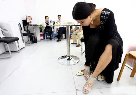 Trước giờ trình diễn ít phút, những người mẫu như cô đi giày cao gót và chờ đợi