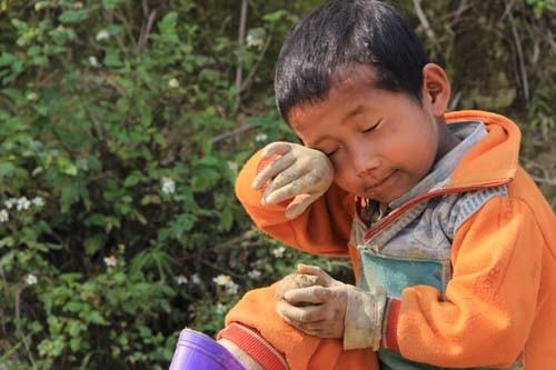 Cậu bé Giàng Su Pao (bản Khằm 1, xã Trung Lý, Mường Lát) ngồi nghịch đất ven vạt rừng với đôi tay lem luốc, lạnh cóng