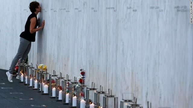 Cô gái hôn lên tên của người thân trong vụ khủng bố 11/9 sau khi đặt hoa và nến ở dưới