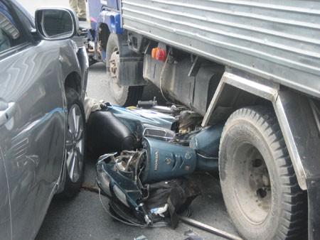 Xe máy bị cuốn vào gầm ô tô.